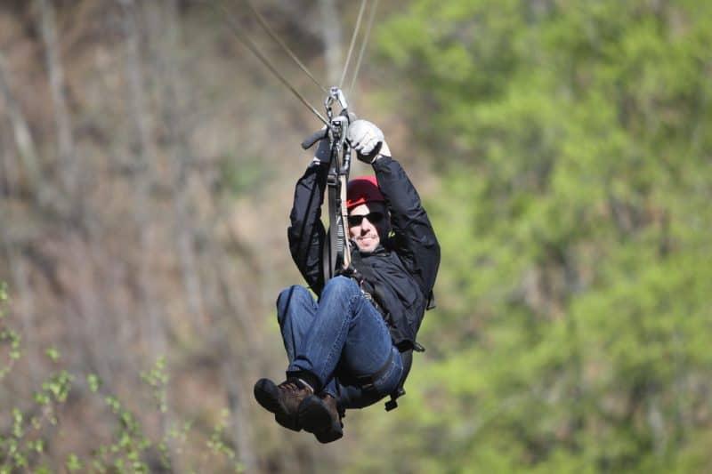 Closeup of man ziplining through the jungle