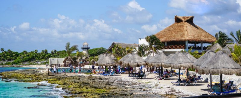 Cozumel beach with thatch umbrellas sheltering lounge chairs