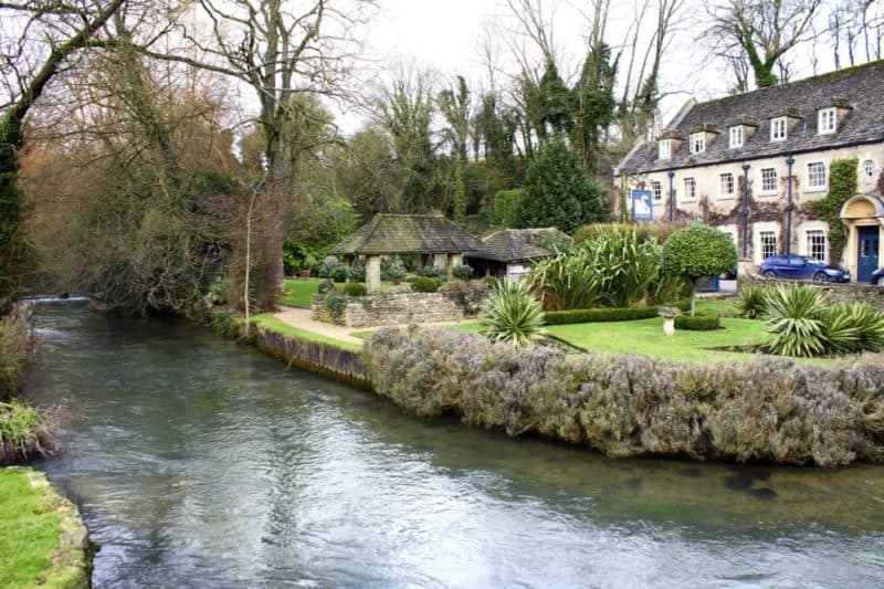 river in front of a house in the cotswolds