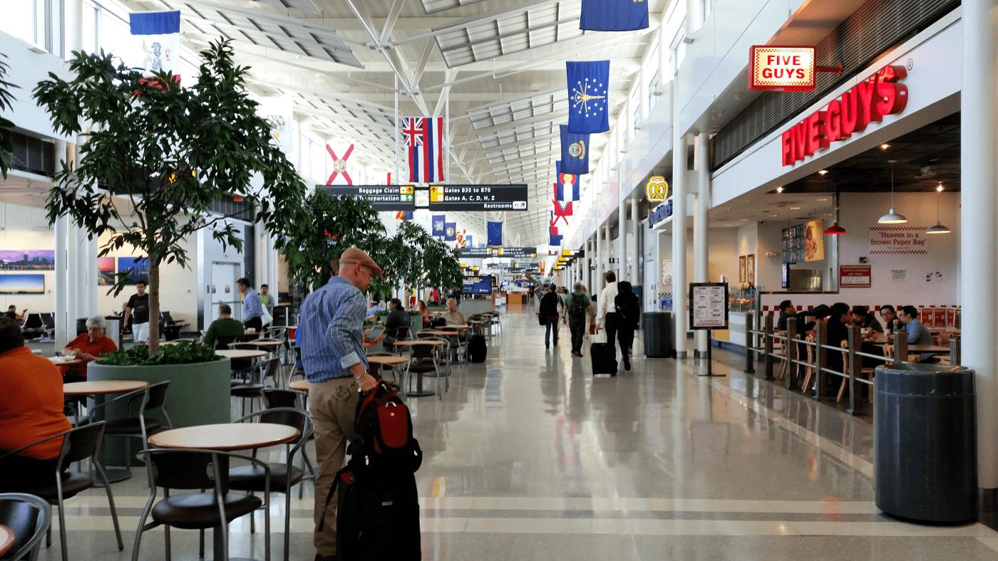 Man wheeling luggage through airport departures area