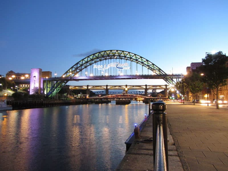 Newcastle quayside at twilight. View down the walkway and River Tyne toward bridge in background.