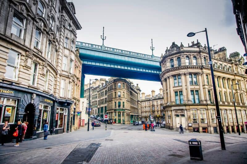 Street in Newcastle with a metal bridge above old buildings