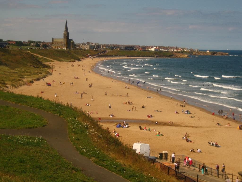Tynemouth Longsands beach bordered by grass and sea. St. George's Church in distance.