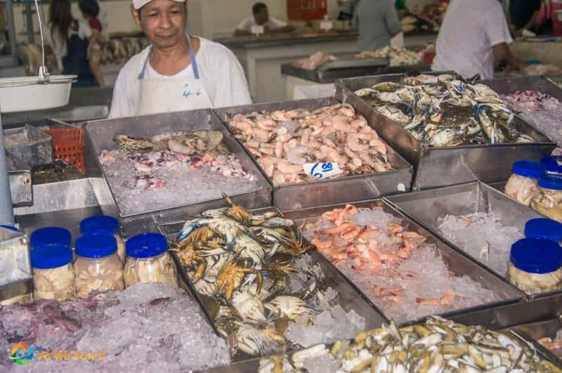 Man stands behind bins of seafood on ice at the fish market in Panama City Panama