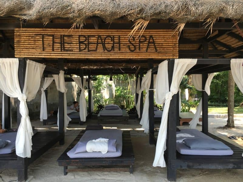 open air pavilion with beds and sign saying the beach spa