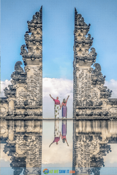 A couple stand at the candi bentar split gate at Pura Lempuyang temple in Bali, with their outer hands raised. Image reflected at ground level.