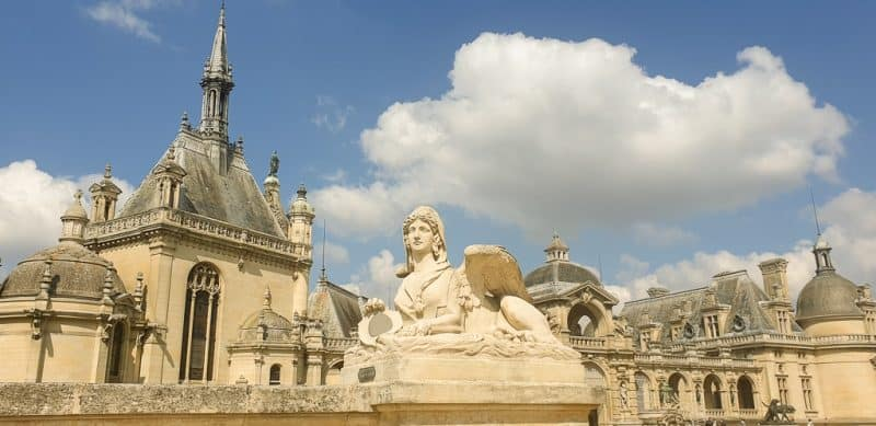 Rooftops of Chateau de Chantilly with sphinx sculpture in the foreground. One of the classic day trips from Paris.