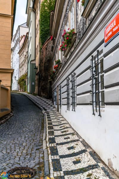 Street and decortive sidewalk curve out of sight on a street in Prague