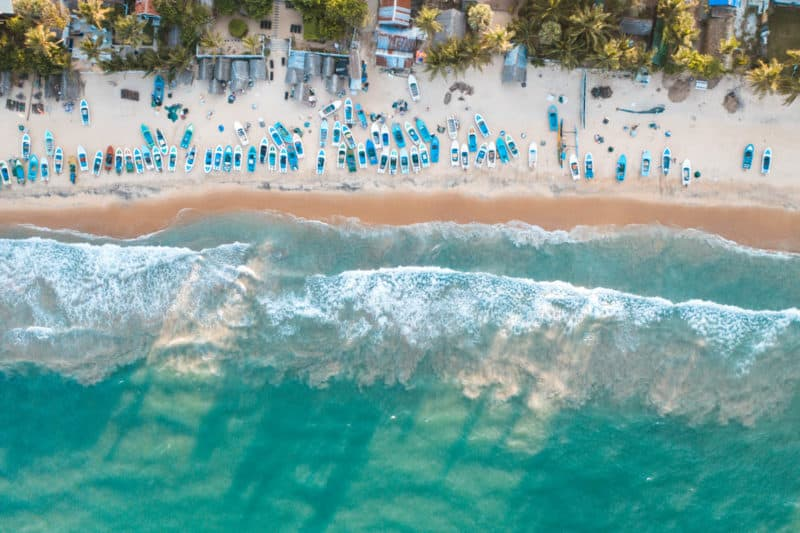 Aerial view of water and people on the beach at Arugam Bay