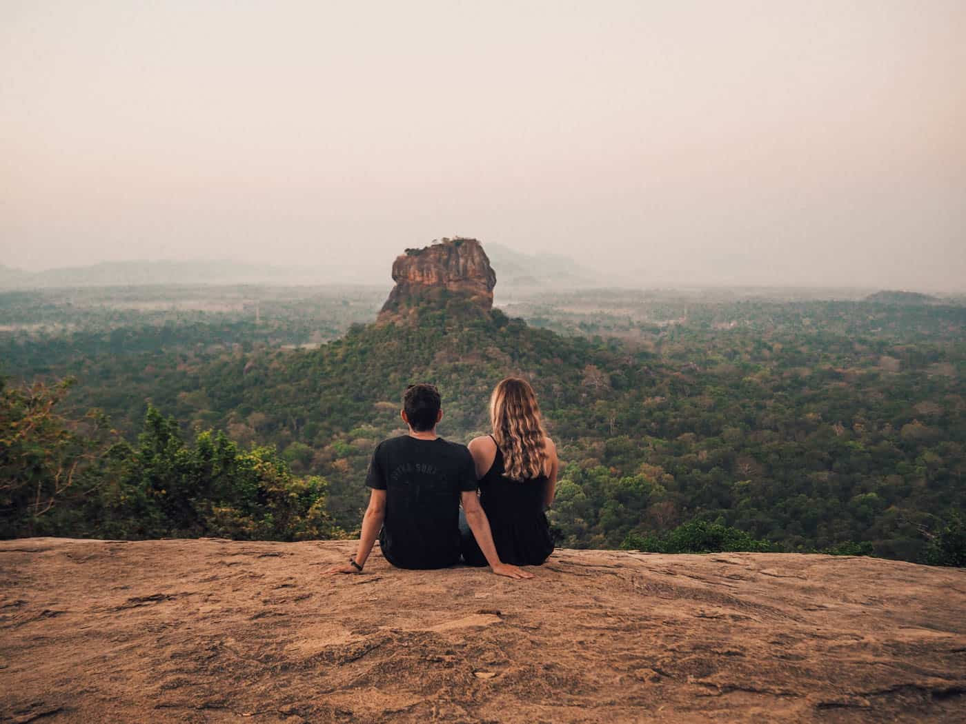 Couple sitting in foreground, with Sigiriya Rock in distance
