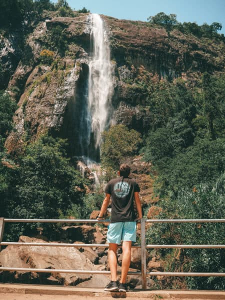 Woman leaning on a railing in foreground looking at Diyaluma Falls in background