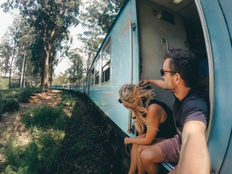 People sitting on the doorway of the Ella to Kandy train