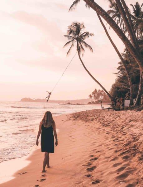 Woman walking toward the palm tree rope swing on Dalawella Beach