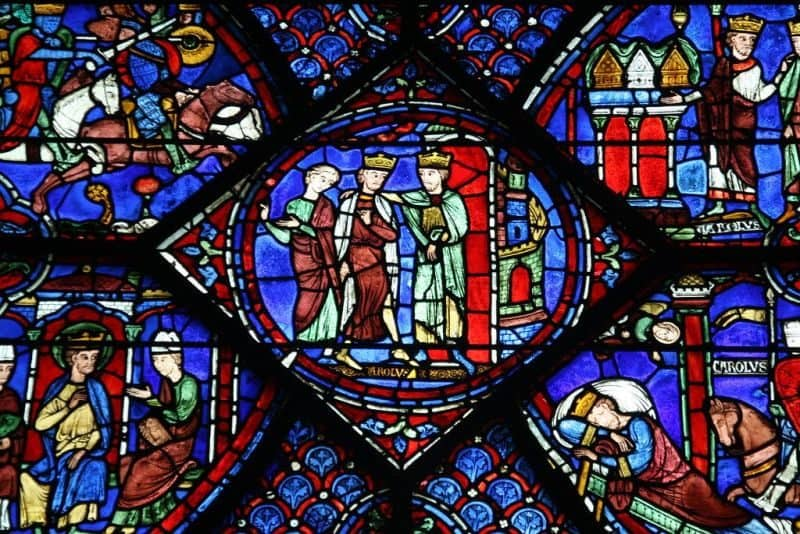 Detail of a stained glass window at Chartres cathedral. Round center image is of two men wearing crowns standing with a woman, and a castle tower in the background.