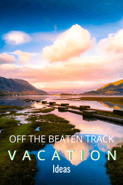 mountains reflecting in the lake at sunset text says off the beaten track vacation ideas