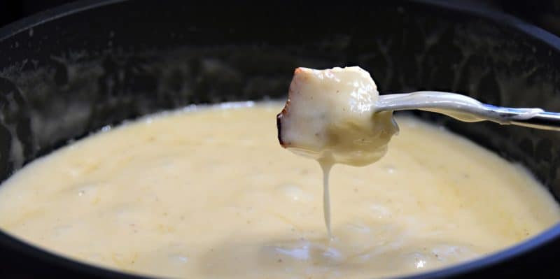 Closeup of a cheese soaked piece of bread dripping cheese back into a pot of bubbling cheese fondue.