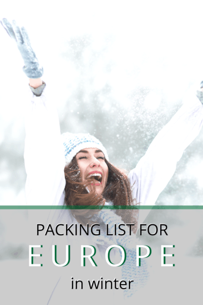 woman rejoicing in the snow with arms extended upwards text says packing list for europe in winter