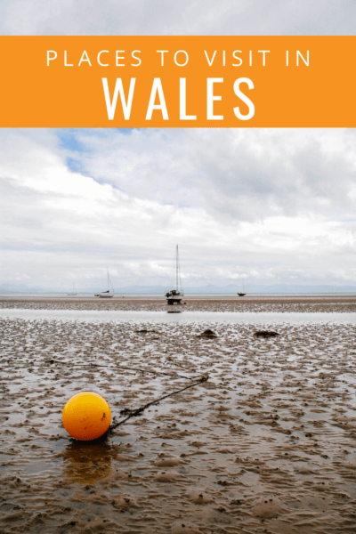 tide out at abersoch with orange bouy up close text says places to visit in wales