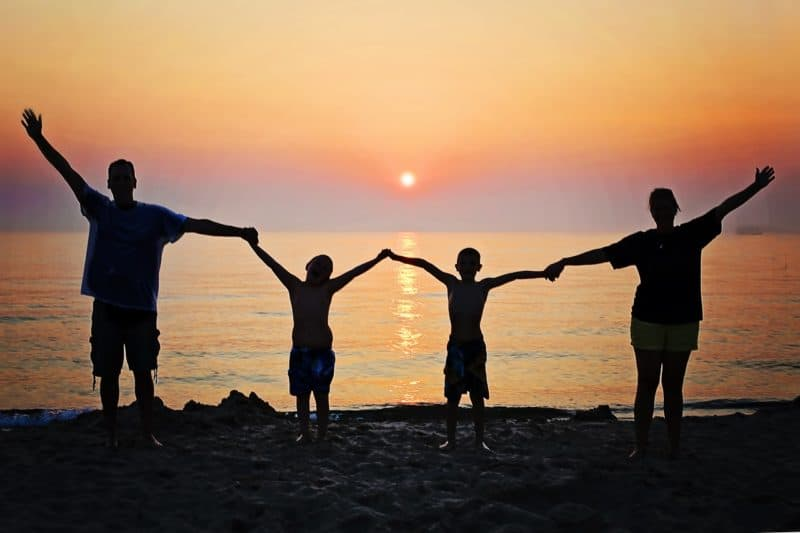 family holding hands on the beach at sunet