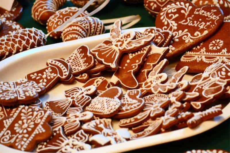 plate full of German lebkuchen in various shapes and sizes. Mostly angels and hearts, all decorated with icing.