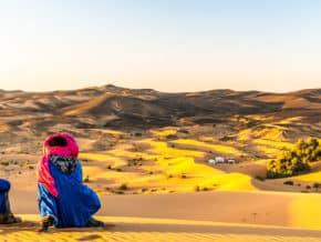 Bedouins enjoying the sunset across the Sahara sand dunes.