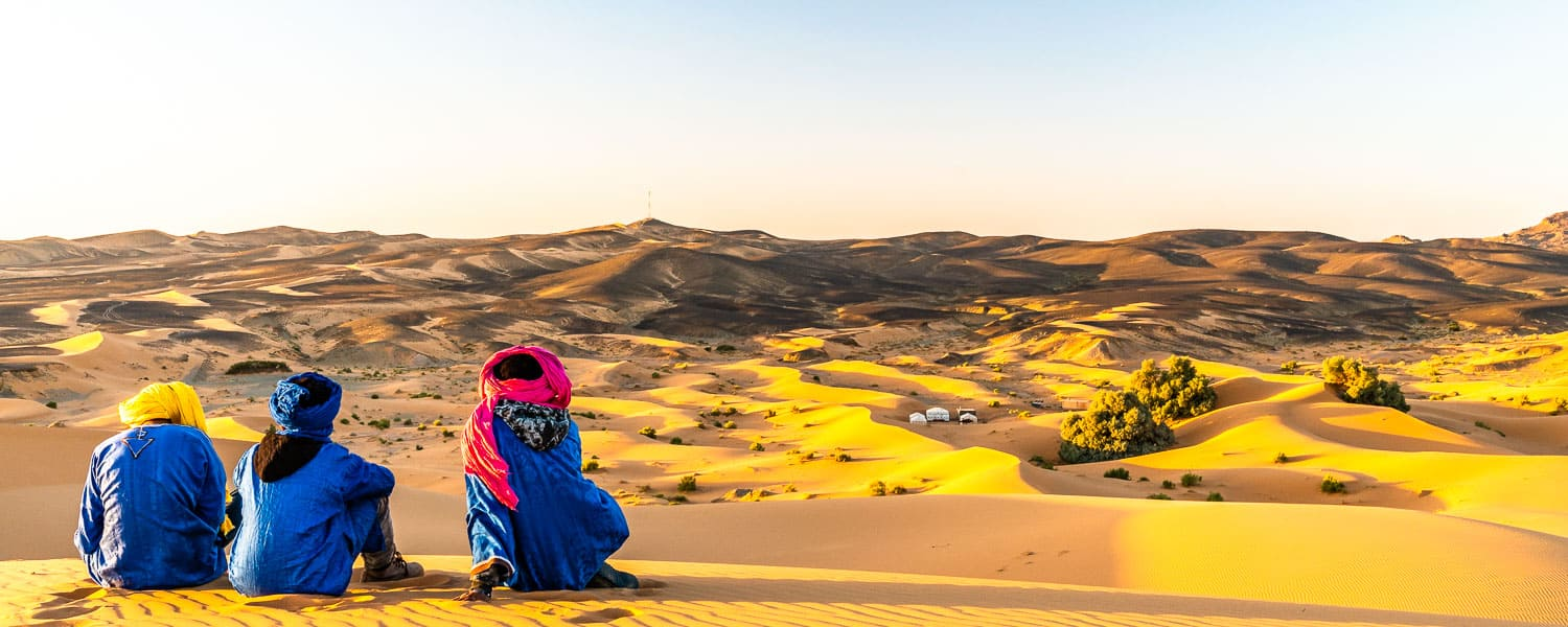 Bedouins enjoying the sunset across the Sahara sand dunes.
