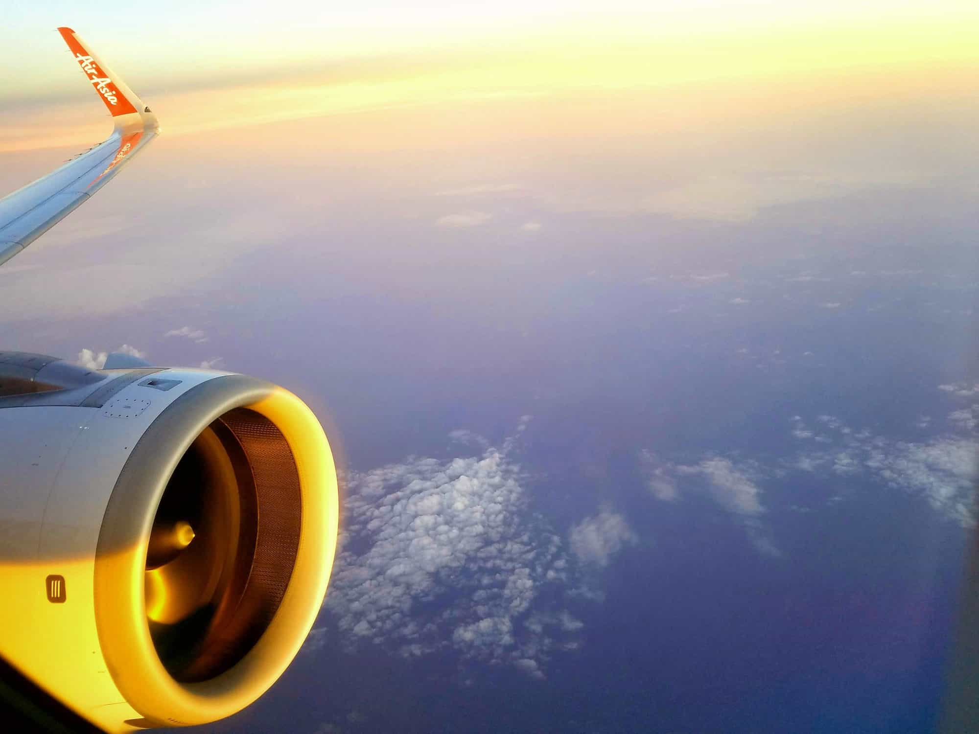 View out airplane window towards the engine at sunset