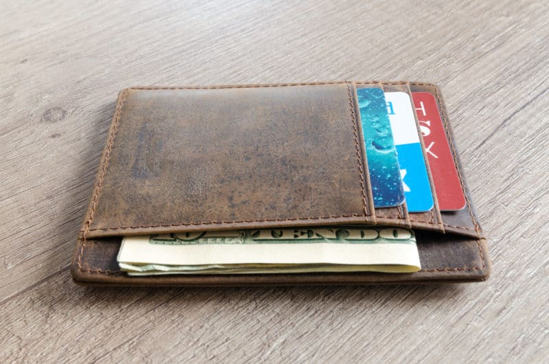 Leather wallet on wooden table with money - be prepared for the cruising add-on costs
