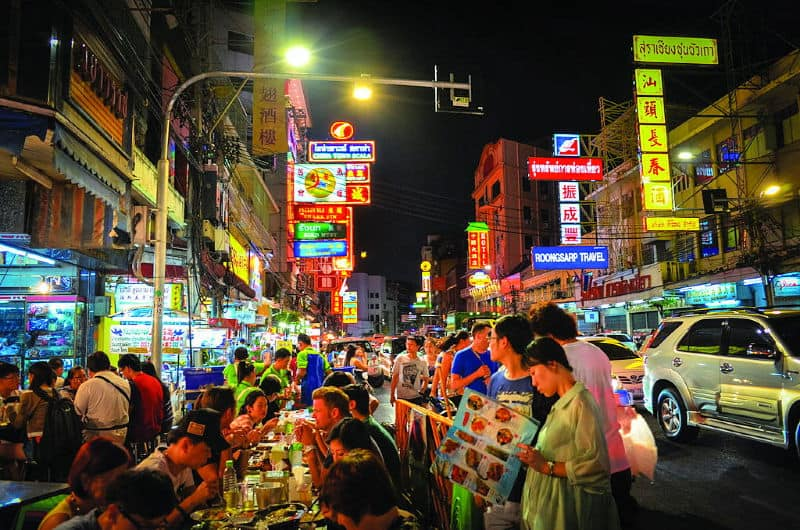 People eating street food on tables on a street in Bangkok's Chinatown