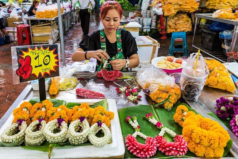 Woman creating a flower garland in Bangkok flower market