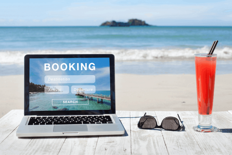 laptop with sunglasses and a drink on the beach. text says booking