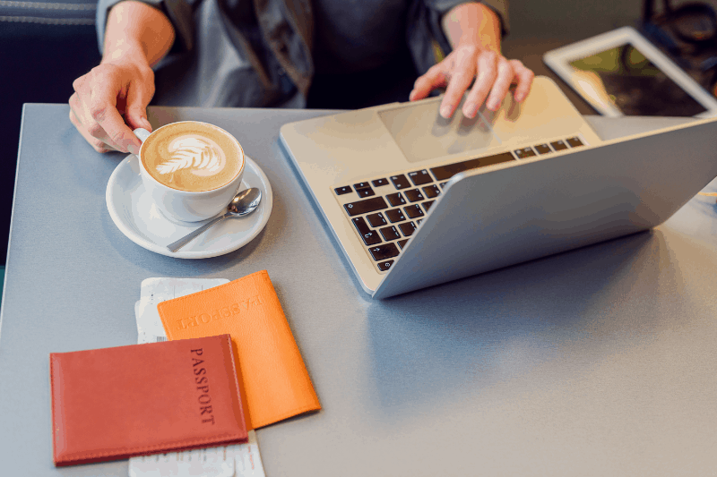 Hands touching a cup of coffee and a laptop with a passport nearby. Illustration of how easy it is to find cheap flight deals from Next Vacay. Just check your inbox.