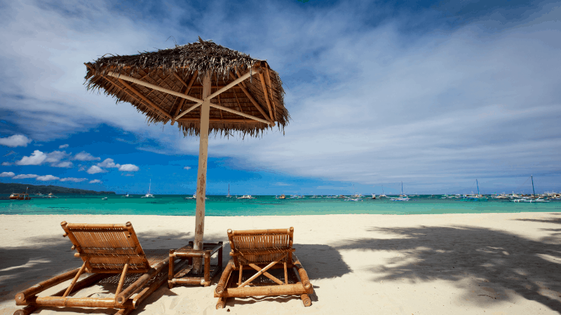 two beach chairs with umbrella on white sand beach at a Boracay resort