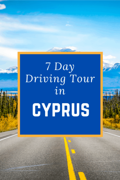 lines painted on road heading toward a mountain text says 7 day driving tour in cyprus