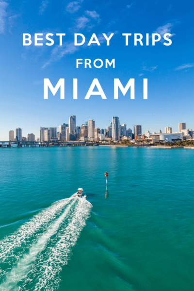 boat on biscayne bay in foreground, miami in background. Text overlay says best day trips from Miami