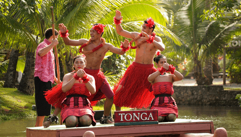 Five people performing at the polynesian cultural center, a top Oahu attraction. Sign on the stage says Tonga