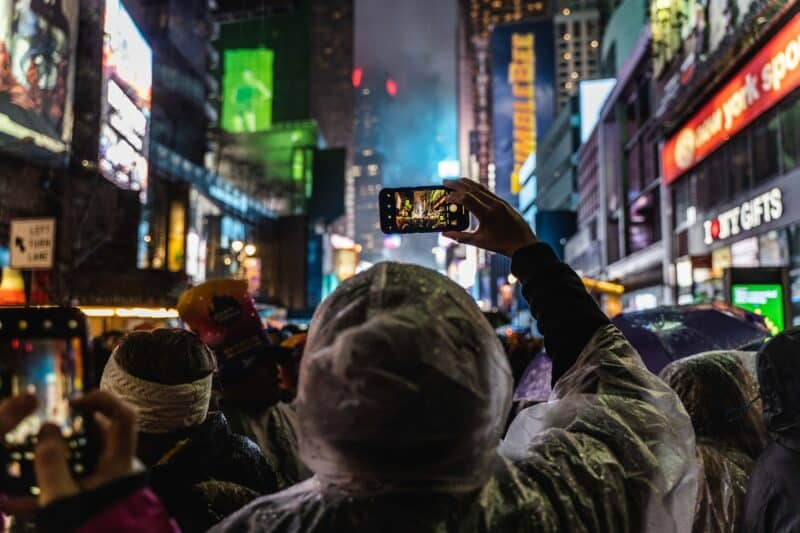 Woman taking a photo at times square in NYC in winter