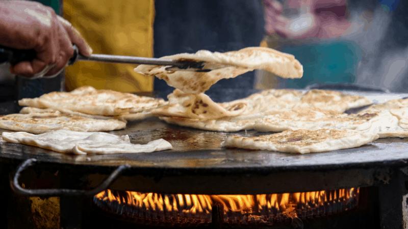closeup of tongs flipping roti canai