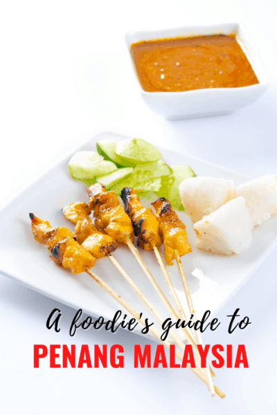 """Chicken satay skewers on a plate with cucumber and rice cakes. Bowl of peanut sauce nearby. Text overlay says """"A foodie's guide to Penang Malaysia"""""""