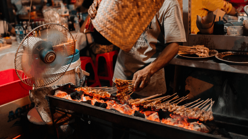grill with skewers of satay over hot coals