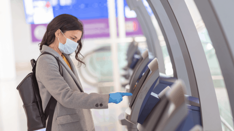 woman wearing mask and gloves and using a ticketing terminal at an airport