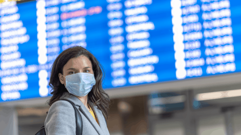 woman wearing a mask and standing in front of a departure board at an airport