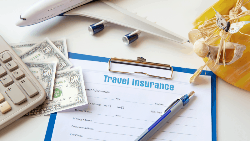 application for pandemic travel insurance on a clipboard, with money, calculator and pen