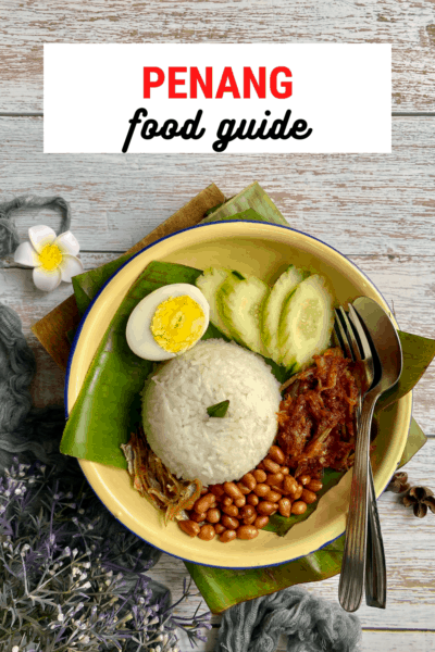 """Bowl with a banana leaf, rice, egg, cucumbers, small dried fish called ikan bilis, and peanuts. Text overlay says """"Penang food guide"""""""