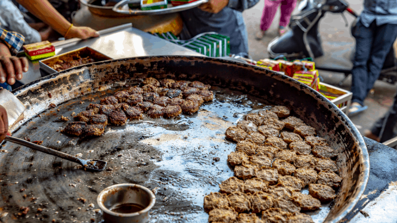 Tunday kebabs being cooked on a street food grill. Popular Indian foods.