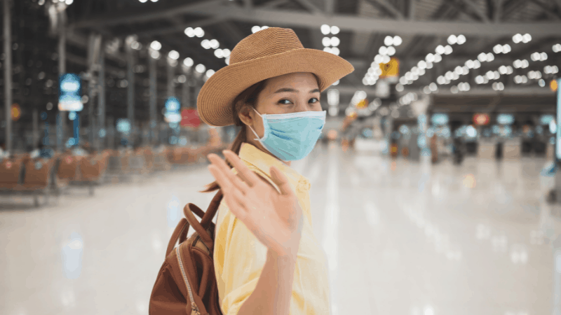 girl wearing a surgical mask in an airport