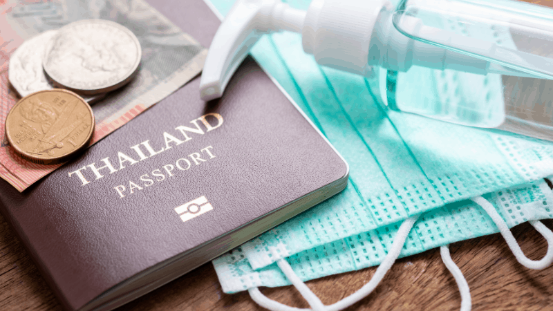 thai coins, passport, surgical mask and hand sanitizer