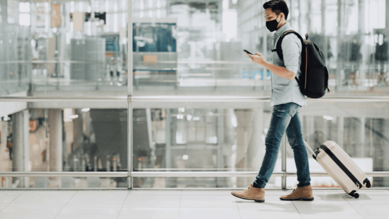 man wearing a mask walking through an airport with his carryon and looking at a phone