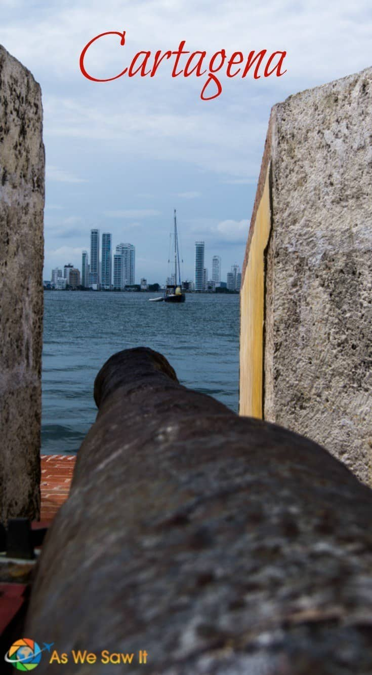 Here's why you'll love Cartagena, the jewel of Colombia's cities. Image of cannon pointing across the bay with Cartagena skyscrapers in the background. Text overlay says Cartagena.