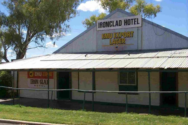 Buildilng with corrugated steel awning across the front. Sign at the peak says Ironclad Hotel. Sign underneath says Emu Export Lager.